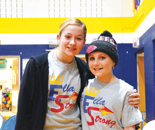 St. Andrew's sixth grader Ella McNeil shares a hug March 24 with close friend St. James-Liberty fifth grader, Maddie Kandlbinder at an assembly at St. James in Ella's honor. (Marty Denzer/Key photo)