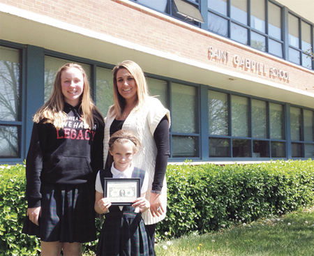 Principal Amy Hogan stands with Tom Adams' grandaughters Olivia and Sophia, who is holding  the framed millionth dollar. (photo courtesy of St. Gabriel Parish)