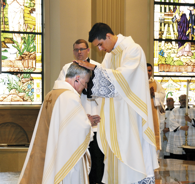 Newly ordained Father Samuel Miloscia gives his first blessing to Bishop James V. Johnston at the Cathedral of the Immaculate Conception on May 28.  He then blessed his parents, siblings and other family members. (Marty Denzer/Key photo)