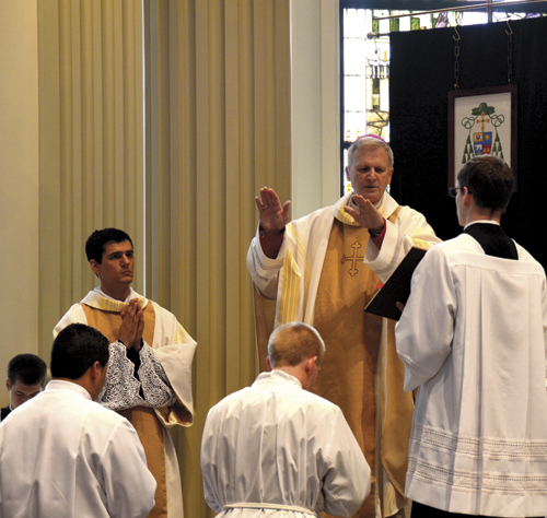 During the Rite of Ordination to the Diaconate, seminarians Jonathon Davis and Olvin Giron-Melia kneel before the Bishop as he says the Prayer of Ordination over them at the Cathedral of the Immaculate Conception on May 21. (Marty Denzer/Key photo)