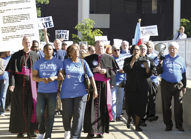 Processing to a June 2 rally against predatory lending at Barney Allis Plaza are advocacy group members, clergy including Kansas City-St. Joseph Bishop James V. Johnston, Jr. and Western Missouri Episcopal Bishop Martin Field, and dozens of the metro community. (Marty Denzer/Key photo)