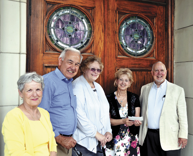 Ed and Cheryl Ann Wills (far right), winners of a trip for 2 to Vatican City through a  Northland Serra Club raffle, hold the check June 25 in front of Our Lady of Sorrows Church with Priscilla Pawlikowski, past president and Wayne Snyder, incoming president, of the Serra Club. (Marty Denzer/Key photo)