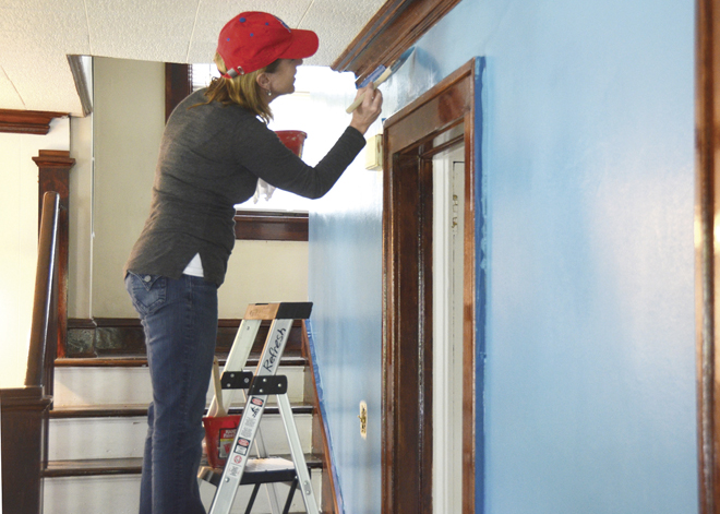 "St. Peter's parishioner Mary Madden, a volunteer for the Refresh-KC project of the parish's Urban Village ministry project, paints a living room near 56th and Paseo. Partnering with the Nazarene Theological Seminary, 60 volunteers painted the interiors of homes in the Blue Hills neighborhood, got to know ""our neighbors"" and refreshed the neighborhood. It's about the paint, and it's not. (Marty Denzer/Key photo)"