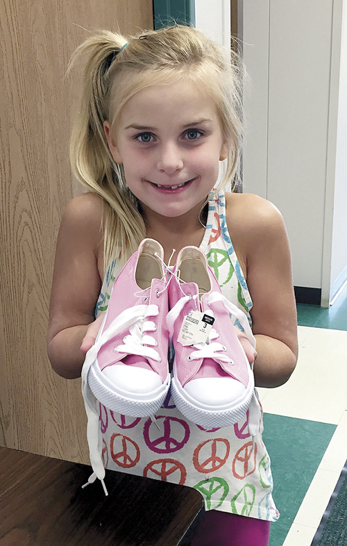 A young girl is incredibly pleased to get a new pair of shoes through the AFL CIO Community Services distribution, thanks to the annual Soles for Christ drive. (Sara Kraft/Key photo)