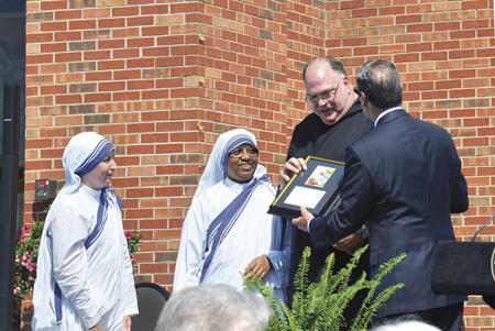 While Sisters Trinidad and Flora, MC, look on, Father Miller and Benedictine President Minnis talk about the 'Do Something Beautiful' award. (Marty Denzer/Key photo)