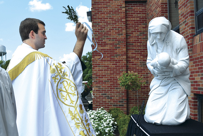 Fr. Simon Baker, Benedictine College Chaplain, blesses the new statue of St. Teresa of Calcutta outside of the Mother Teresa Center for Nursing & Health Education on the Benedictine College campus. (Photo courtesy Benedictine College)