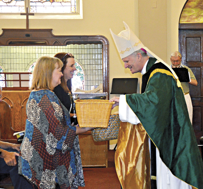 Barb Deane, president of Our Lady of Hope School and Mary Delac, principal, offer the congregation's gifts to Bishop Johnston during the dedication Mass at Guardian Angels Church, Sept. 11. (Marty Denzer/Key photo)