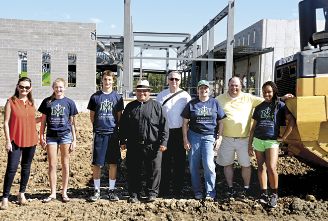 At what will be the main entrance to St. Michael the Archangel High School are (l-r) Principal Jodie Maddox, two students who will attend when it opens, President Father Richard Rocha, Schools Superintendent Dr. Dan Peters, diocesan Construction Manager Martha Kauffman, Jeremy Lillig, diocesan Director of Stewardship and Development and another committed student. (Marty Denzer/Key photo)