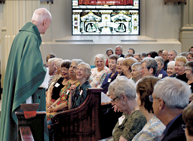 Jesuit Father Tom Curran greets Sisters of St. Joseph of Carondelet during the homily of the Mass honoring the community's 150 years of service in Kansas City. (photo courtesy Sisters of St. Joseph)