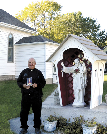 Standing near the century-old statue of the Sacred Heart on the grounds of Sacred Church in Hamilton, Father Phil Luebbert holds 'The Glories of Mary,' by St. Alphonsus Liguori, a focal point in his prison ministry. (Marty Denzer/Key photo)