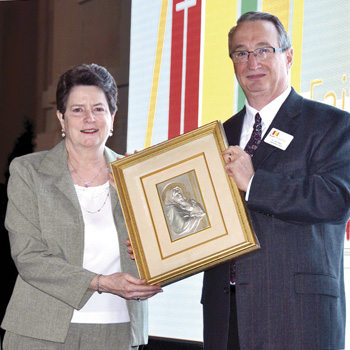 Retiring Holy Cross teacher Helen Pueschel shows off her Icon Award with Diocesan School Superintendent Dr. Dan Peters. (Marty Denzer/Key photo)