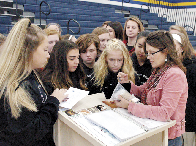 Raegan Ratterman shows interested eighth graders one of the visual aids she uses during her sidewalk counseling for Project Rachel. Ratterman was one of the speakers at the Respect Life Education Day held at St. Pius X High School on Oct. 25. (Joe Cory/Key photo)