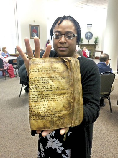 Arhives assistant Tara Harris very carefully holds a Coptic Bible dating from the 14th century. (Megan Marley/Key photo)