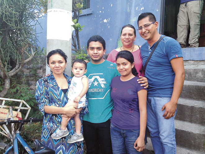 Rafael, a scholarship student, and his family, members of St. Peter's sister parish, San Francisco de Asis pose with Arturo, (right) the scholarship coordinator. (Photo courtesy Nancy Caccamo)