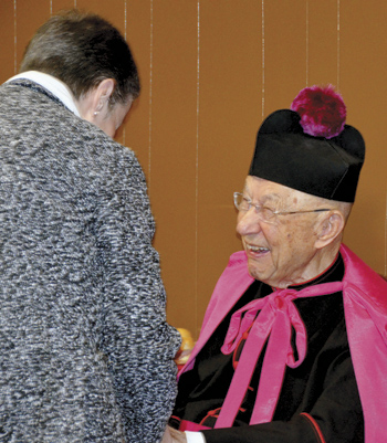 Seated during the reception, Msgr. Blacet greeted well-wishers with a laughing smile. The line to shake his hand wrapped around the room. (Marty Denzer/Key photo)