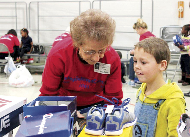 Presentation parishioner Margaret Gouger delights a Faxon Elementary student with a new pair of shoes on Dec. 15. (Photo courtesy Anna Mitchell, Presentation Parish)