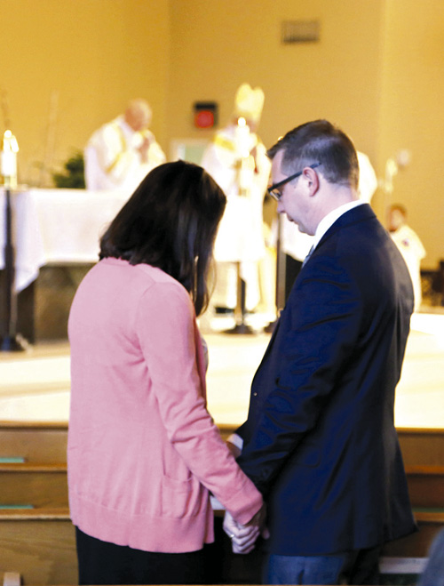 A husband and wife hold hands as Bishop Johnston blesses all couples gathered at the Mass for the World Day of Marriage, held Sunday, Feb. 12 at St. Thomas More parish in Kansas City. (Megan Marley/Key photo)