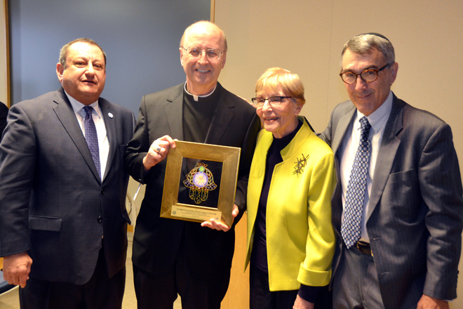 Abbot Primate Gregory Polan displays the plaque he received from Marvin Szneler, Jewish Community Relations Bureau/American Jewish Committee Exec. Director at a luncheon in his honor Feb. 16. WIth them are retired Rabbi Alan Cohen and Judy Hellman, JCRB/AHC Associate Exec. Director. (Marty Denzer/Key photo)